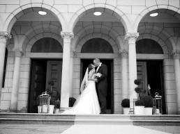Video Still: Bride and groom kiss in front of their wedding venue